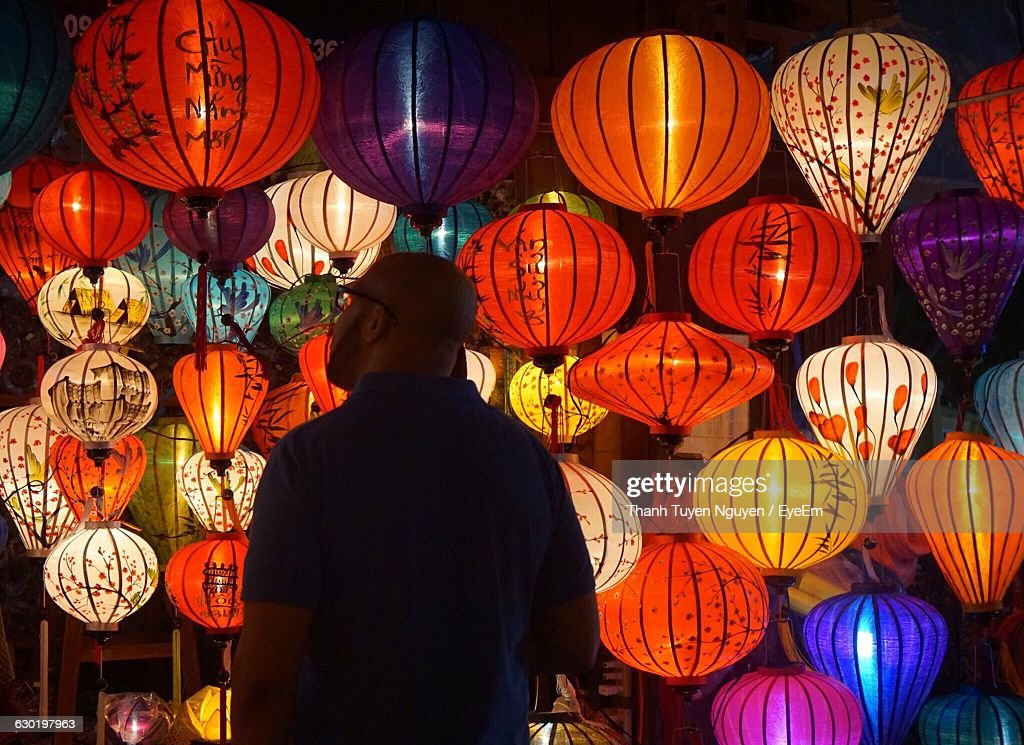 Mature Man Standing In Front Of Illuminated Lanterns At Night : Photo
