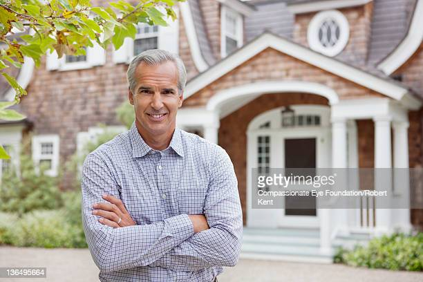 Mature man standing in front of residential home