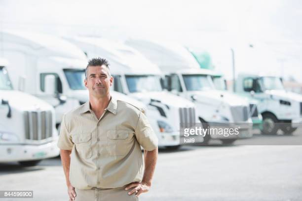 Mature man standing in front of semi-trucks