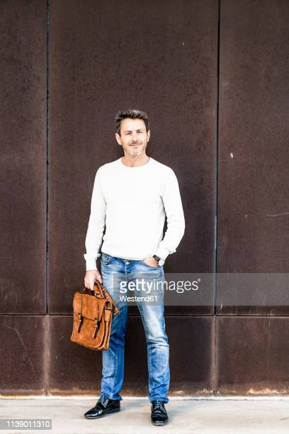 mature man standing in front of steel facade, holding briefcase - hands in pockets stock pictures, royalty-free photos & images