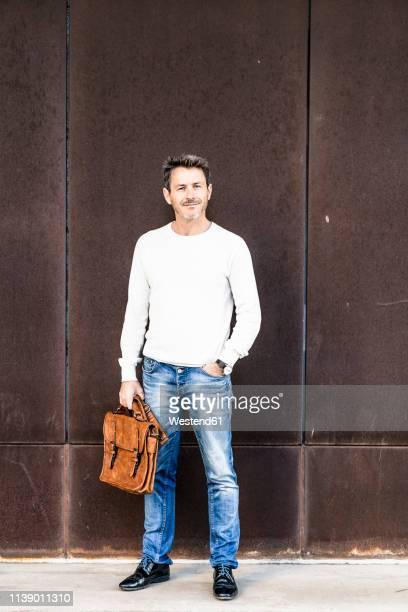 mature man standing in front of steel facade, holding briefcase - handen in de zakken stockfoto's en -beelden