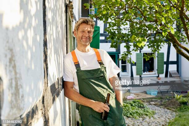 mature man standing in his garden wearing apron, holding a bottle of beer - ハーフティンバー様式 ストックフォトと画像