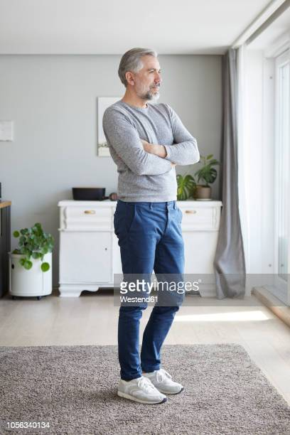 mature man standing in his living room looking out of window - standing photos et images de collection
