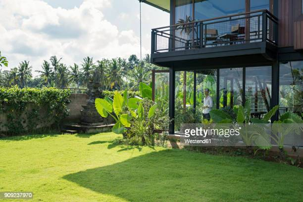 mature man standing in his modern house, looking through window - only mature men stock pictures, royalty-free photos & images