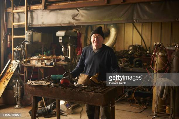 mature man standing in his workshop. - daniel funke stock-fotos und bilder