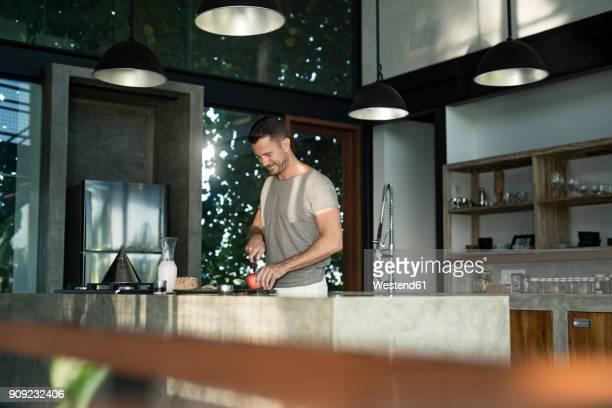 mature man standing in kitchen, preparing healthy breakfast - ein mann allein stock-fotos und bilder