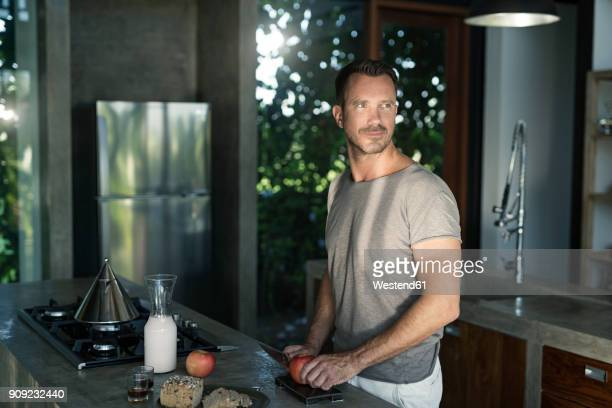 mature man standing in kitchen, preparing healthy breakfast - ein mann allein stock-fotos und bilder