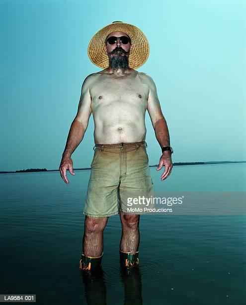 mature man standing in water, portrait - marque de bronzage photos et images de collection