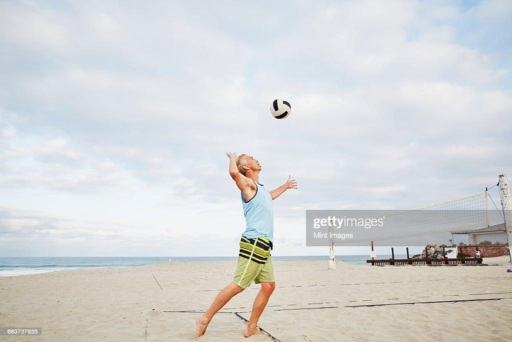 Mature man standing on a beach, playing beach volleyball.  : Stock Photo