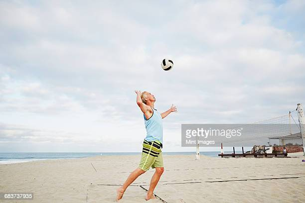 mature man standing on a beach, playing beach volleyball.  - strand volleyball der männer stock-fotos und bilder