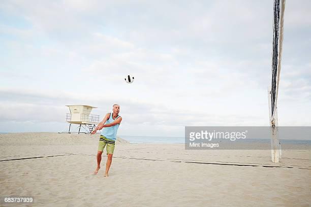 mature man standing on a beach, playing beach volleyball.  - strand volleyball der männer stock-fotos und bilder