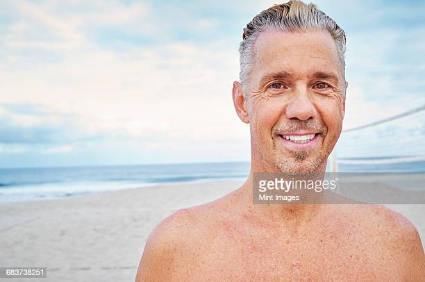 Mature man standing on a beach, smiling at camera.