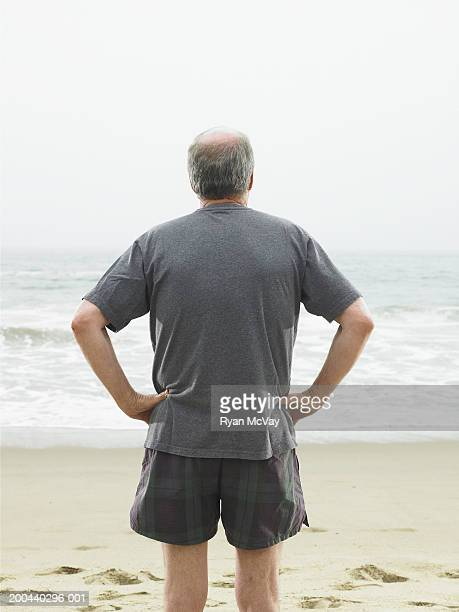 Mature man standing on beach, rear view