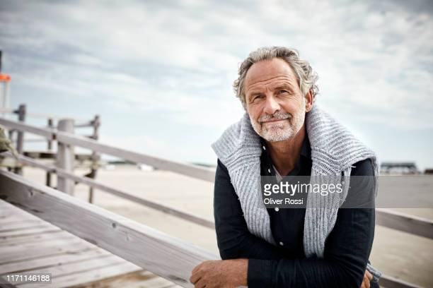 mature man standing on boardwalk on the beach - cinquantenne foto e immagini stock