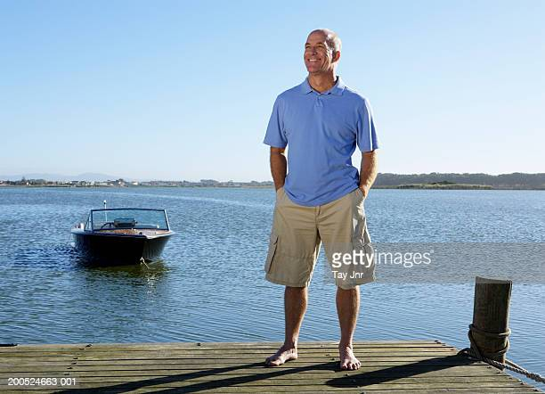 Mature man standing on jetty, smiling