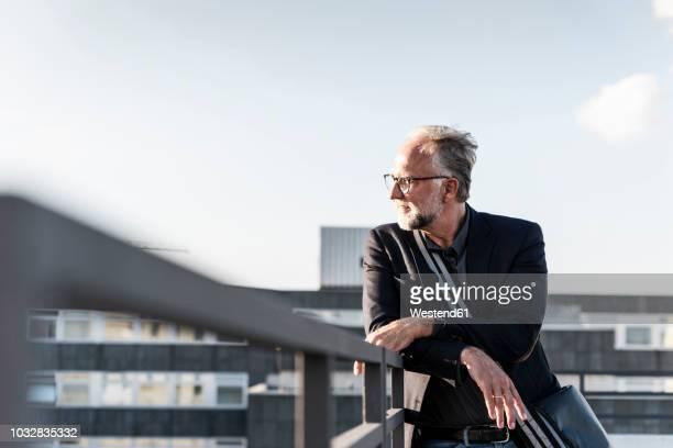 mature man standing on rooftop, leaning on railing - architektur stock-fotos und bilder