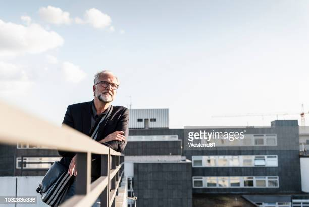 mature man standing on rooftop, leaning on railing - garde corps photos et images de collection