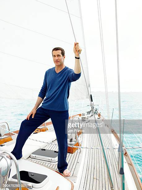 Mature man standing on sailboat