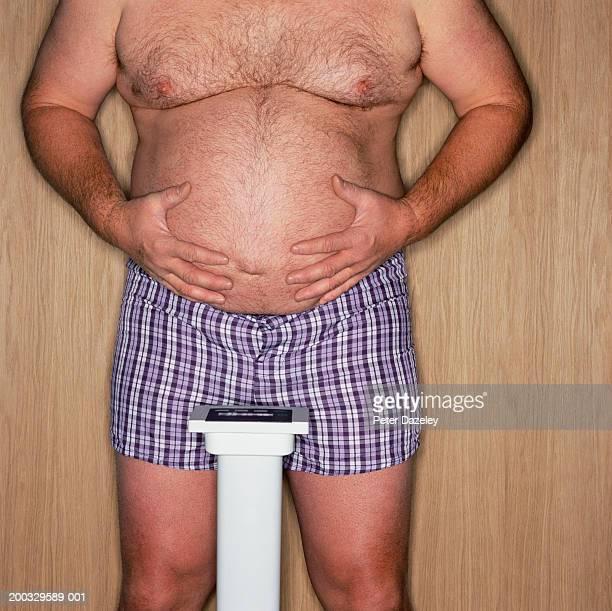 mature man standing on scales holding belly, mid section - barriga de cerveja imagens e fotografias de stock