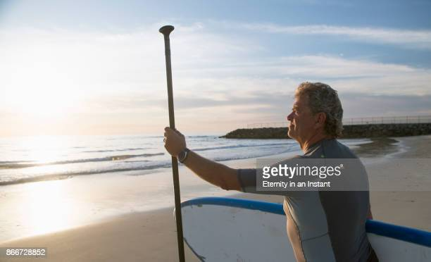 mature man standing on the beach with his paddleboard looking at the ocean. - paddleboard stock photos and pictures