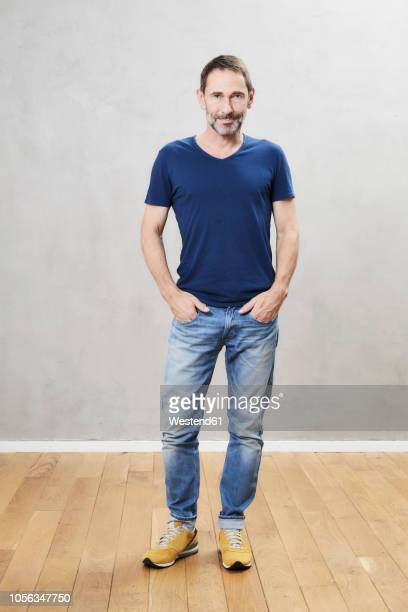 mature man standing on wooden floor - stehen stock-fotos und bilder