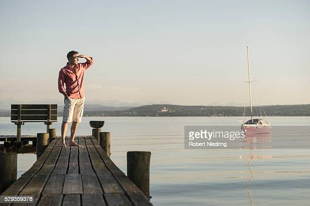 Mature man standing on wooden pier and looking at distance, Bavaria, Germany,