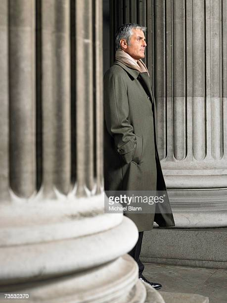 Mature man standing outside, in between large columns