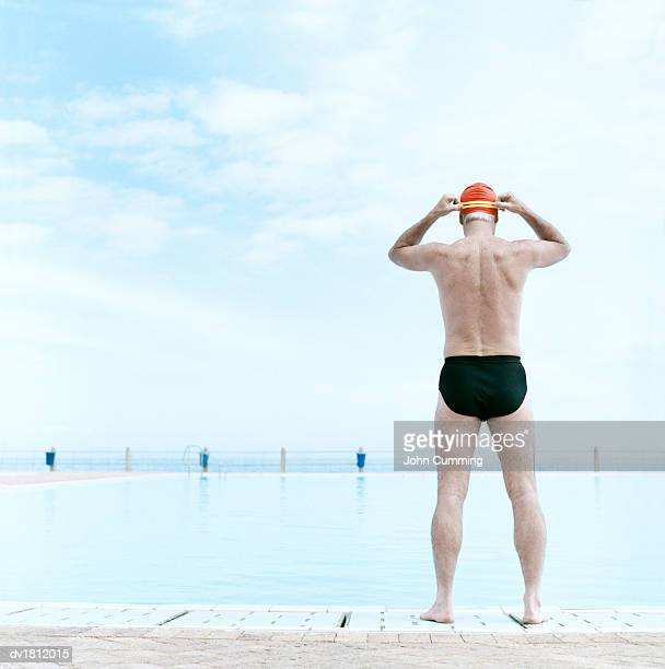 Mature Man Standing Poolside and Preparing to Swim