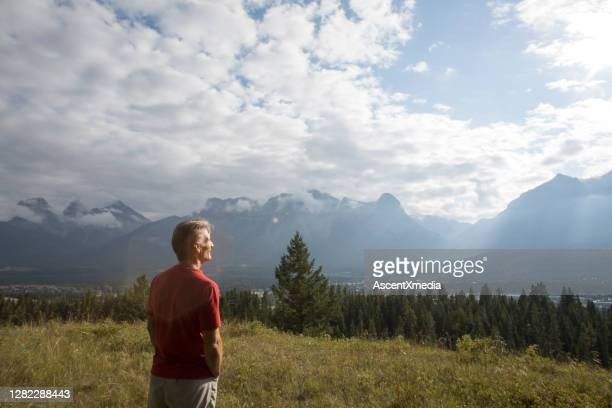 mature man stands in mountain meadow and watches sunbeams across the valley - one mature man only stock pictures, royalty-free photos & images