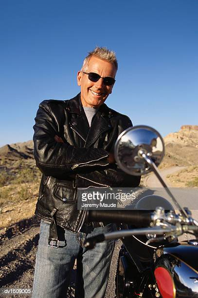 mature man stands next to a stationary motorbike in the desert - next to stock pictures, royalty-free photos & images