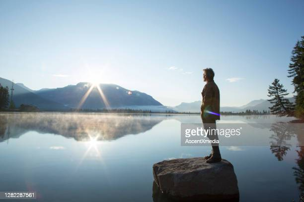 mature man stands on rock, in lake, and watches sunrise - tranquil scene stock pictures, royalty-free photos & images