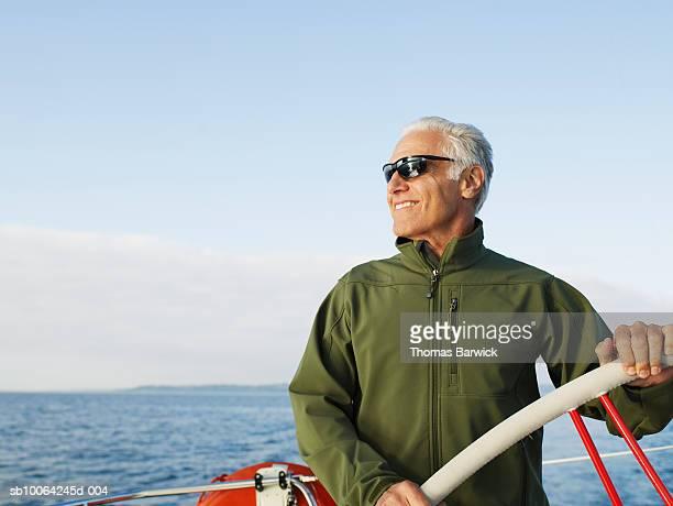 Mature man steering sailboat, looking away, smiling