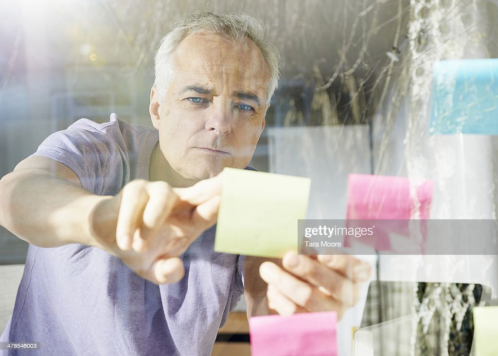 mature man sticking down lost it note : Stock Photo