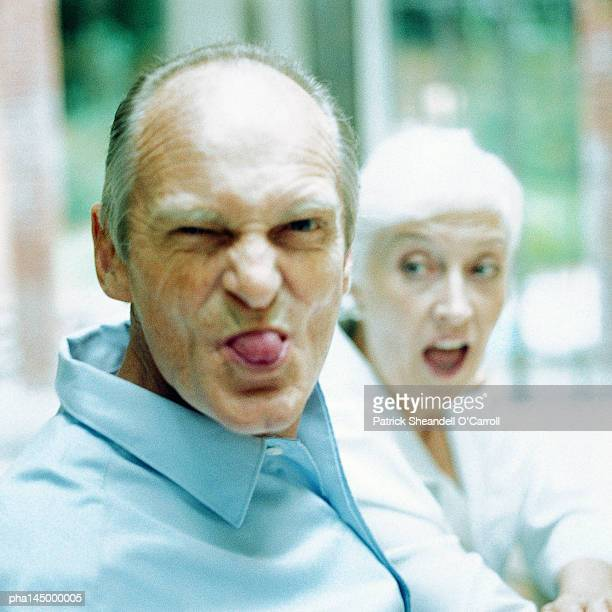 Mature man sticking out tongue, woman in background