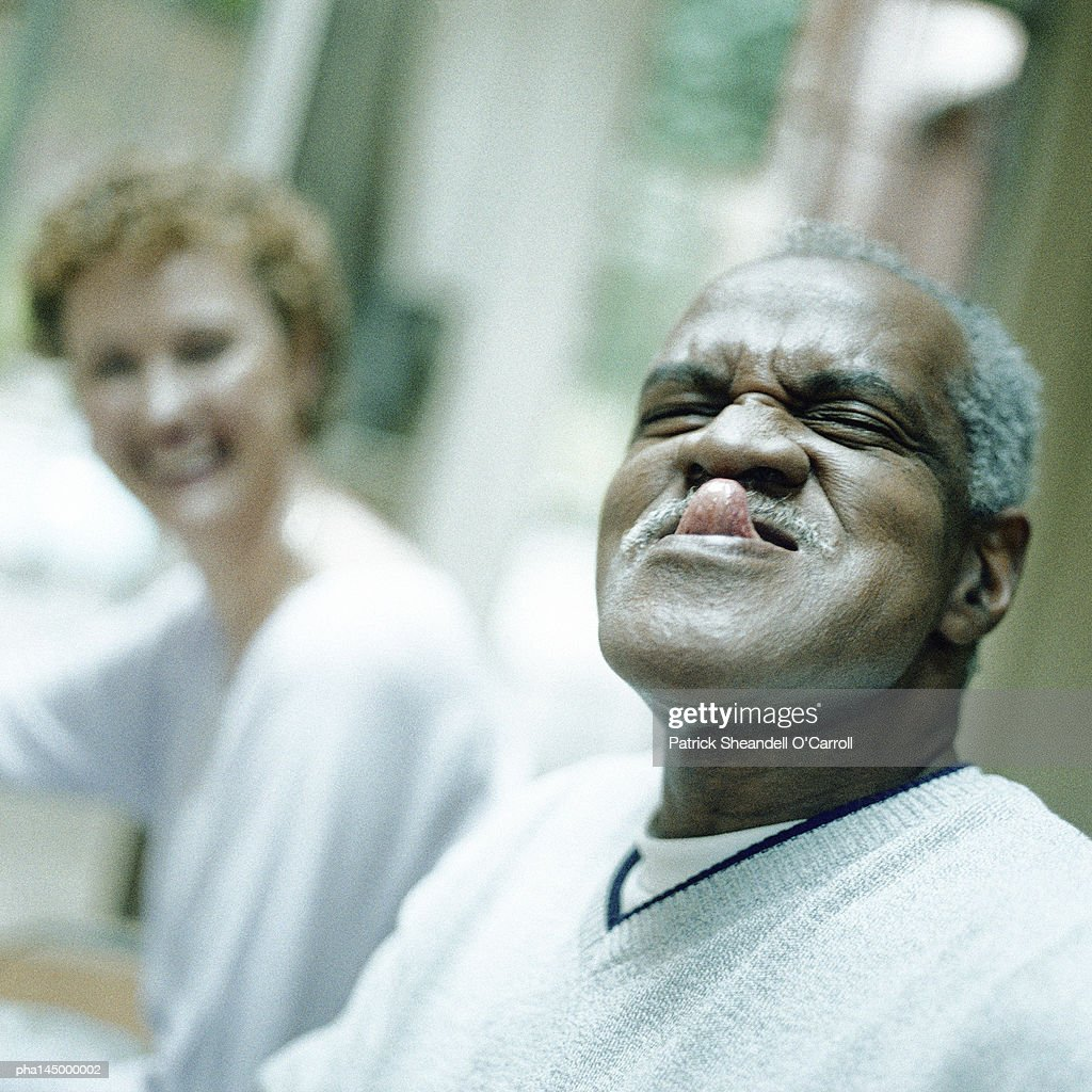 Mature man sticking out tongue, woman smiling in background : Stockfoto