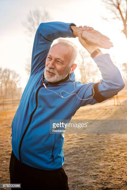 mature man stretching arms in public park - active seniors stock pictures, royalty-free photos & images