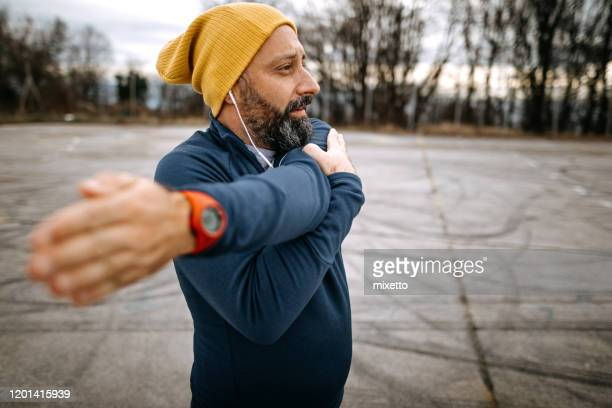 mature man stretching before running - warming up stock pictures, royalty-free photos & images