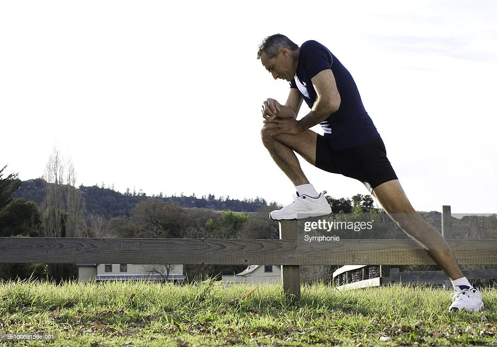 Mature man stretching legs on fence, side view : Stockfoto