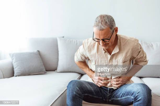 mature man suffering from stomachache at home - stomach ulcer stock pictures, royalty-free photos & images