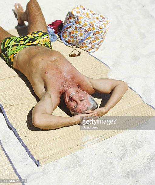 mature man sunbathing on beach, portrait, elevated view - shorts stock pictures, royalty-free photos & images