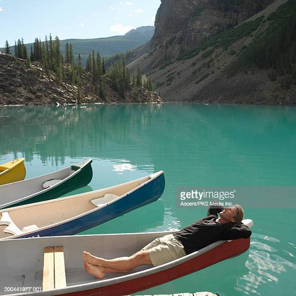 mature man sunning in moored canoe, sunrise, summer - small boat stock pictures, royalty-free photos & images