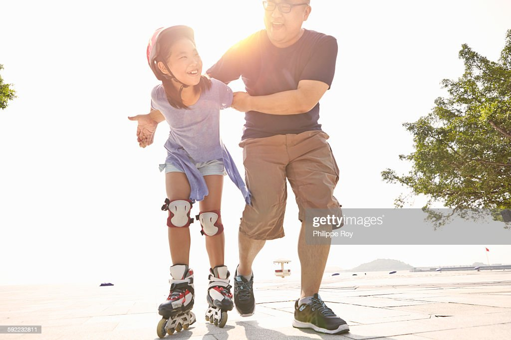 Mature man supporting daughter rollerblading at beach, Zhuhai, Guangdong, China : Stock Photo