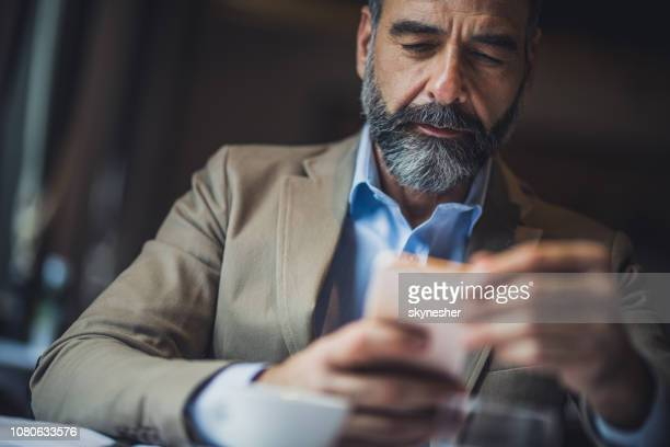 mature man surfing the internet on his smart phone. - smart casual stock pictures, royalty-free photos & images