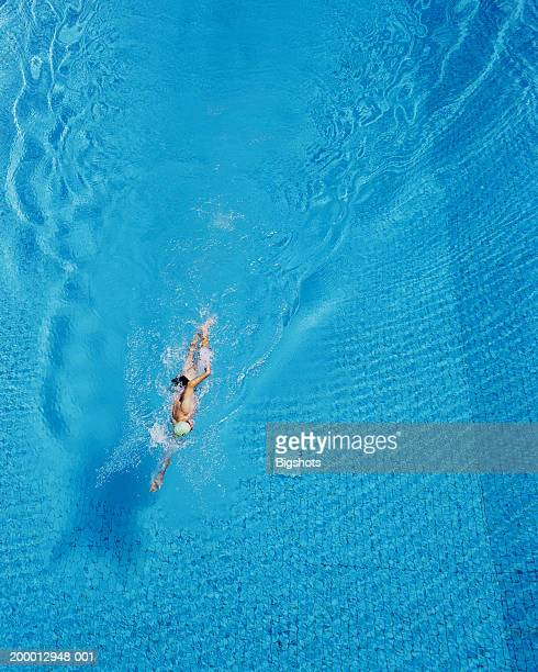 Mature man swimming front crawl in pool, overhead view