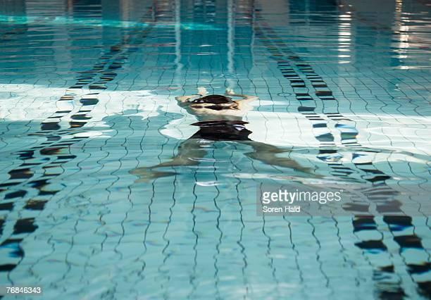 Mature man swimming underwater in swimming pool