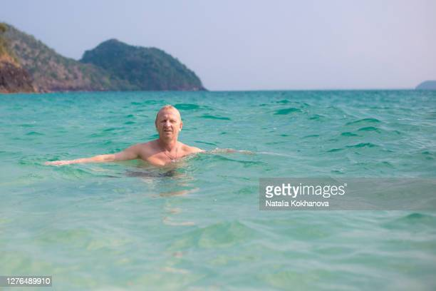 mature blond man swims clear sea