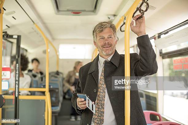 Mature man taking city bus, holding smartphone