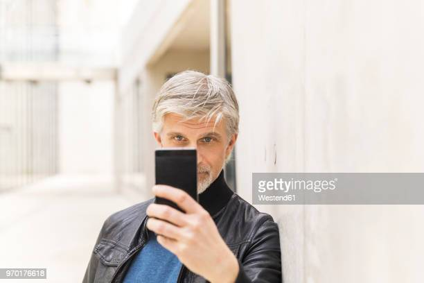 Mature man taking selfies with his smartphone