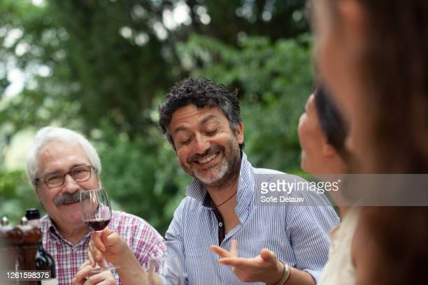 mature man talking at outdoor meal - italian culture stock pictures, royalty-free photos & images