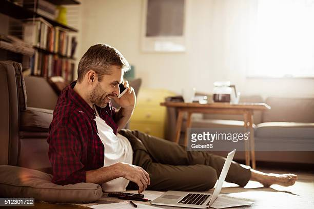 Mature man talking on mobile phone at home